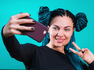 Portrait of young attractive hipster woman with dyed colorful african braids making selfie photo on smartphone isolated on turquoise background. Exotic girl smiling.