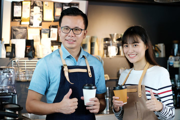 Young asia man and woman barista holding a disposable coffee cup and thumb up with smiling face at cafe counter background, small business owner, food and drink industry