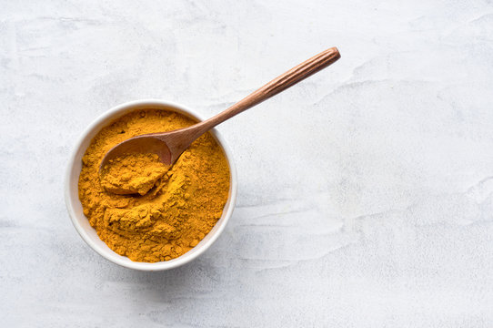 Golden turmeric powder and wooden spoon. Concrete background. Traditional indian spice. Top view.