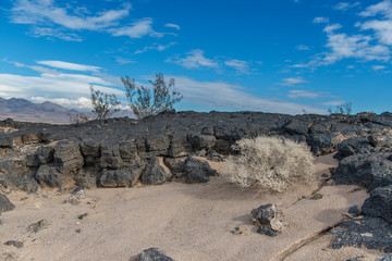 Beautiful Desert scene showing ancient lava flow against a cloudy blue sky in the Mojave Desert off of route 66