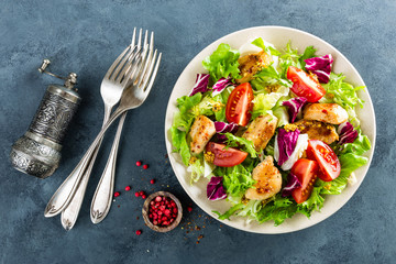 Fresh vegetable salad bowl of tomatoes, cucumbers, italian mix, lettuce and grilled chicken breast on table. Fried chicken meat, fillet with salad. Healthy food