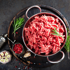 Cooking mince. Raw ground veal meat with ingredients for cooking on black kitchen table. Fresh minced meat, top view
