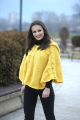 Pretty girl in a yellow knitted poncho standing position, smilin