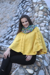 Pretty girl in a yellow handmade knitted poncho, smiling and che