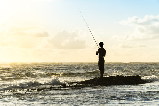 Sunrise Rock Fishing at the Beach in Oahu, Hawaii - a Man's Silhouette Casting Out a Line Against the Crashing Waves of the Ocean