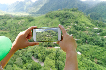Traveler take a photo green tree mountain by smartphone on long holiday - Traveling and Holiday of concept