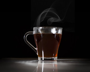 A glass with hot soaring tea on a black background.