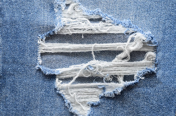 Jeans in wash blue with rip. Denim background, texture. Ripped destructed detail, close up.