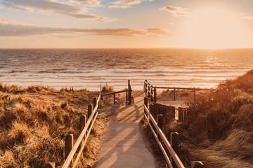Holztreppe mit Blick auf das Meer beim Sonnenuntergang