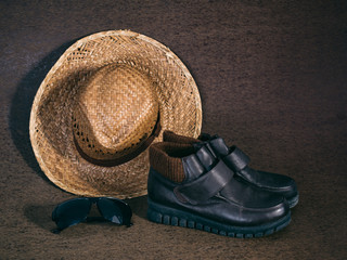 Leather shoes, sunglasses and weaving hat on brown background