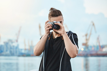 Hunting for best shots. Portrait of attractive urban photographer with vintage camera taking photos near sea, walking around city to picture every interesting moment, searching for inspiration