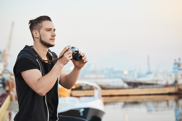 Dreamy talented cameraman impressed with beauty of nature while taking photos on camera, looking at blue sky, standing in harbour near sea. Handsome guy capturing nice shots of seaview while walking