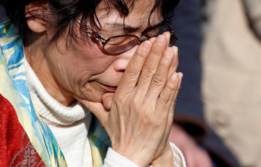 Woman attends a moment of silence at 2:46 p.m., the time when the magnitude 9.0 earthquake struck off Japan's coast in 2011, during a rally in Tokyo