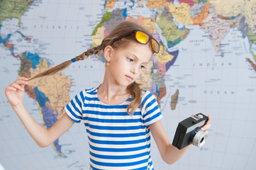 pretty little caucasian girl holding vintage camera and her pigtails on background of world map