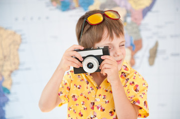 handsome little kid in yellow shirt and sunglasses takes shot with vintage camera on world map background
