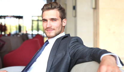 Portrait of happy young businessman sitting on sofa in hotel lobby.