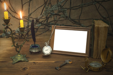 Empty photo frame with copy space and diary book of adventurer on wooden table with compass and rusty key in the light of burning candle. Vintage background. Traveller concept. Explorer.