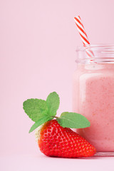 Fresh strawberry smoothie or milkshake in mason jar decorated mint on pink pastel background. Healthy food for breakfast and snack.