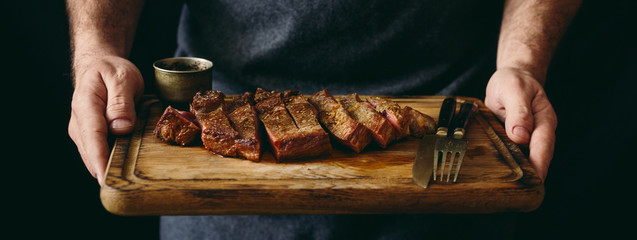 Foto auf AluDibond Steakhouse Man holding juicy grilled beef steak with spices on cutting board