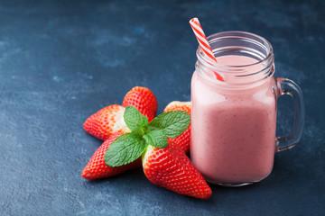 Strawberry smoothie or milkshake in mason jar on dark blue table. Healthy food for breakfast and snack.