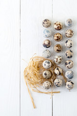 Quail eggs in a package on a white wooden background..