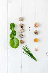 Quail eggs, green sticks onions and garlic cloves on a white wooden background. Food concept.