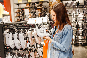 happy young woman customer choosing pair of sneakers shoes and buying it in clothes store, casual shopping concept