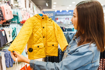 Woman mother buyer chooses clothes for her child in baby shop, fashion motherhood concept