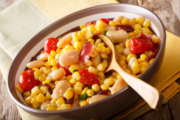 Salad of oil beans, tomatoes, peppers and bacon close-up in a bowl. succotash. horizontal