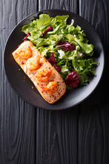 Baked salmon with prawns and honey sauce with a side dish of salad mix close-up on a plate. Vertical top view