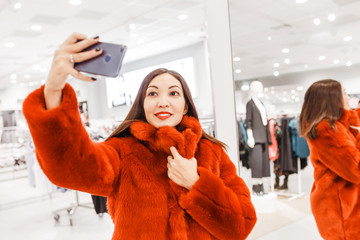 Asian woman, a buyer tries on a bright coat of artificial fur, the concept of shopping and leisure