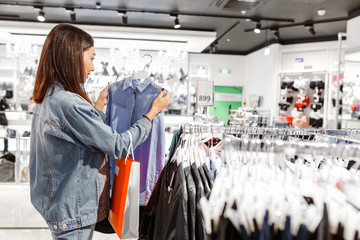 Woman shopper customer choosing shirt and other clothes in a fashion store