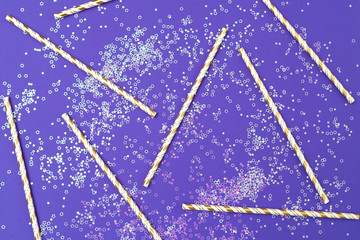 Holiday and festive straws on an ultraviolet background with sparkles. Flat lay