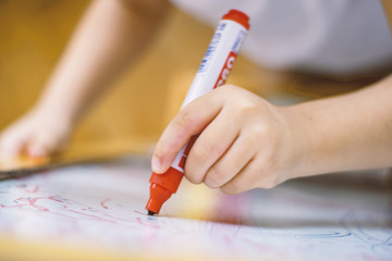Child holding a pencil in whiteboard closeup