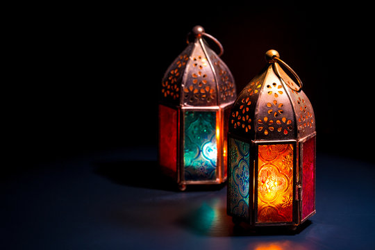 Two colorful oriental Lamp lanterns burn with candles with color reflection on dark black background for Ramadan and other islamic muslim holidays, space for text