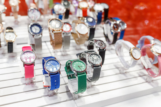 layout of many colorful wrist watches for woman at the window of a store