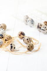 Fresh quail eggs in a white wooden table..