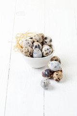 Fresh quail eggs in a white bowl on a white wooden table..