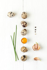 Minimalistic still life with quail eggs, garlic and shiny onion on a white wooden background.