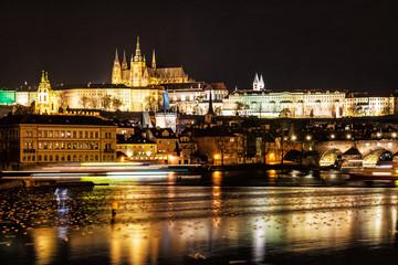 Prague castle and Charles bridge mirroring in Vltava river, night scene