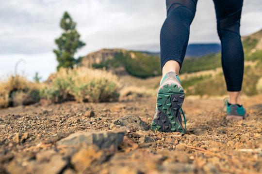 Sole of shoe walking in mountains on rocky footpath