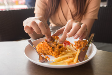 Fried chicken in young woman hand select focus, Hand with fried chicken blur background, Close-up Fried chicken
