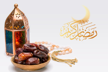 Ramadan Kareem Festive, close up of oriental Lantern lamp with dates on wooden plate and rosary on white background. Islamic Holy Month Greeting Card