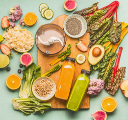 Detox drinks  smoothie making concept. Various healthy fresh fruits, vegetables, seeds, nuts, kale and chard leaves with bottles and mixer on light mint table background with cutting board, top view