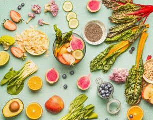 Healthy food ingredients flat lay with various fruits , vegetables, seeds and nut on light mint background. Mixer for detox drinks making, top view. Dieting and clean eating concept