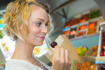 attractive young grocery clerk tasting cherry in grocery store