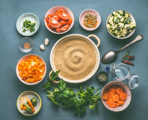 Food flat lay with couscous and vegetarian cooking ingredients in bowls on gray background, top view