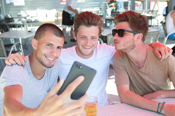 three friends taking a selfie and making faces