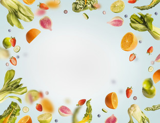 Various flying or falling summer fruits,berries and vegetables on light blue background, frame. Healthy detox food layout concept