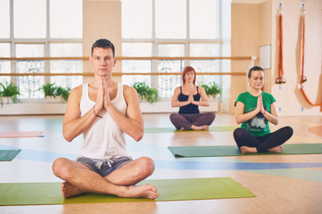 Group of young sporty people practicing yoga lesson with instructor, sitting in Padmasana exercise, Lotus pose with folded hands in namaste
